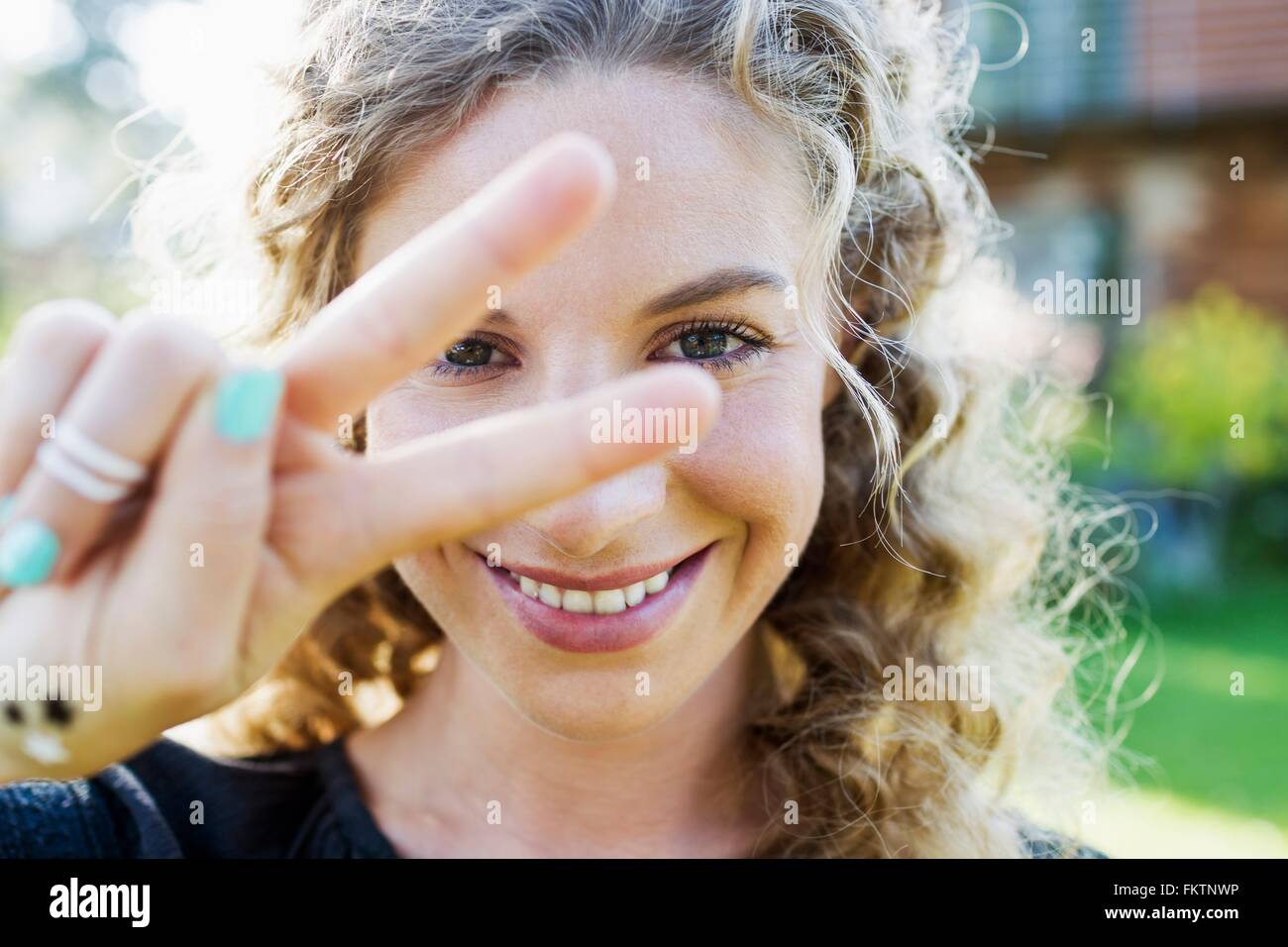 Young woman making peace sign with hand - Stock Image