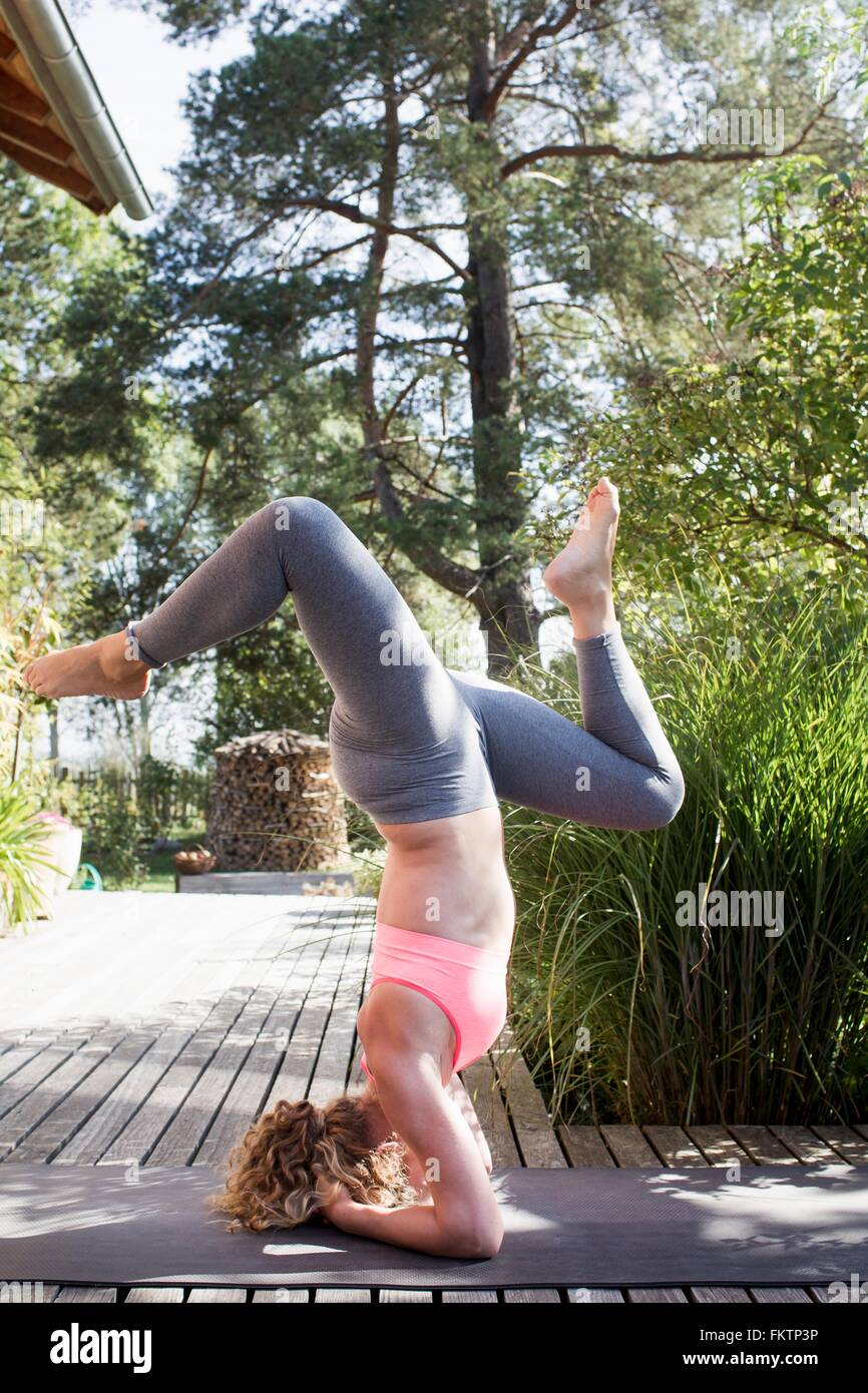 Young woman doing headstand with legs apart - Stock Image