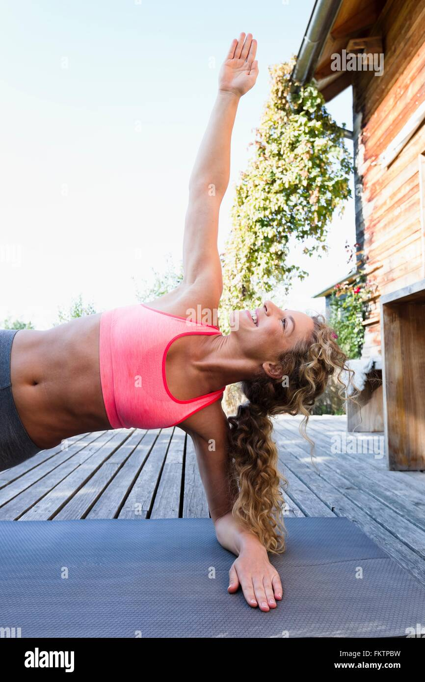 Young woman in side plank pose - Stock Image
