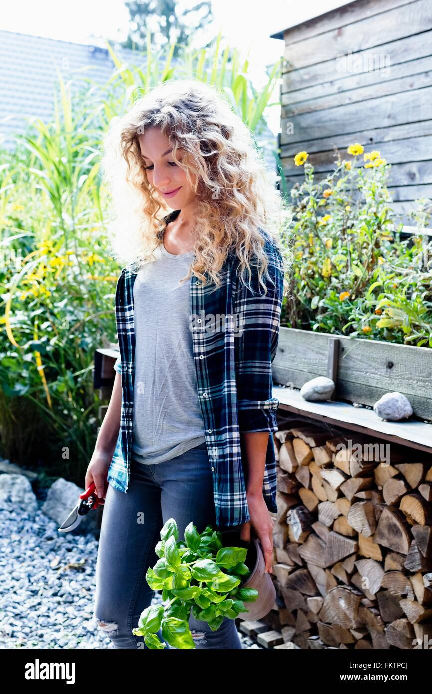 Young woman with curly blonde hair in garden, portrait - Stock Image