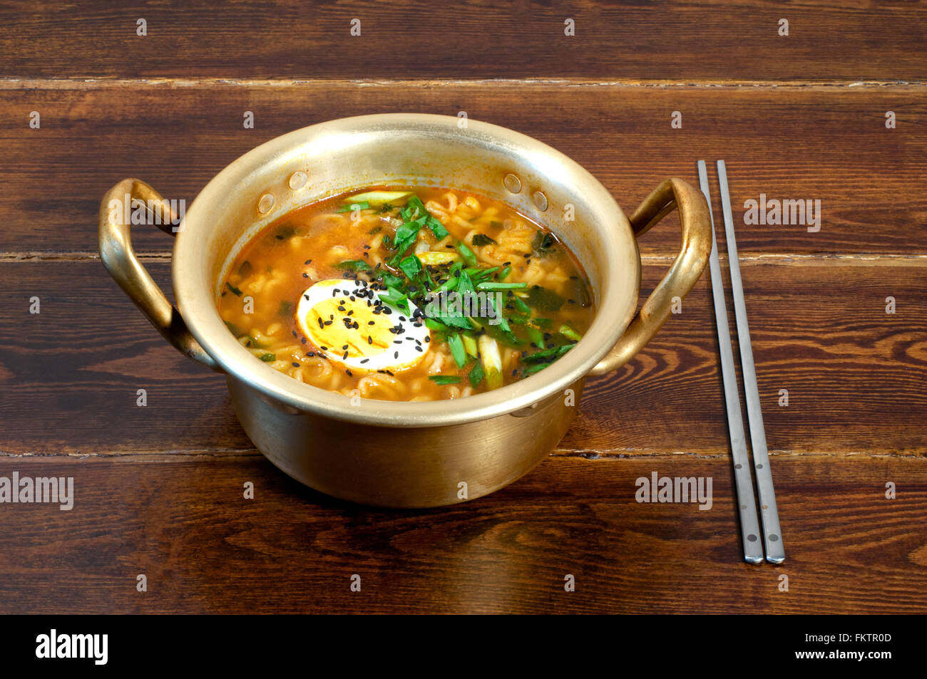 Korean ramen with egg and green onion on golden pan - Stock Image