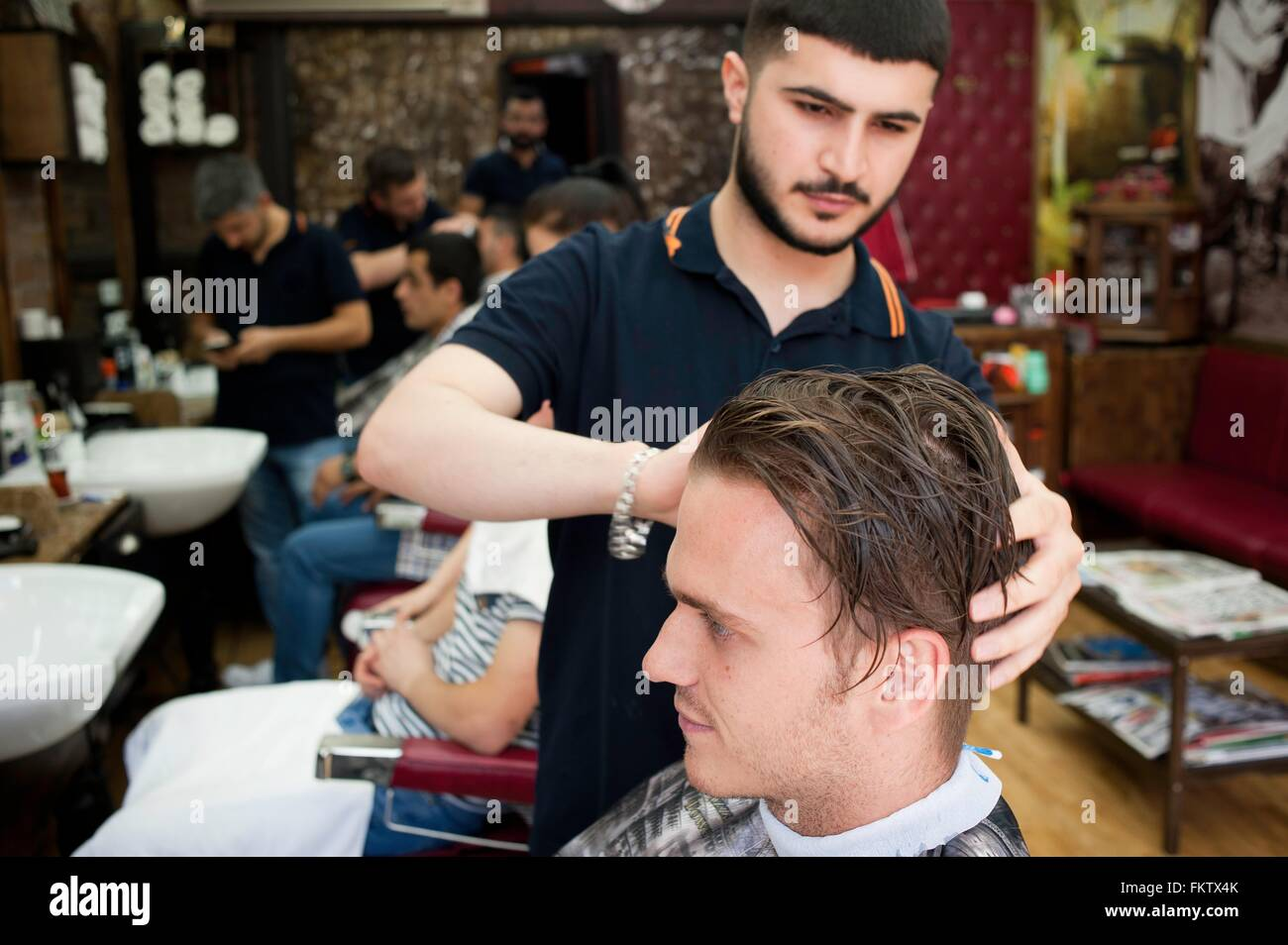 Hairdresser in barbershop cutting young mans hair - Stock Image