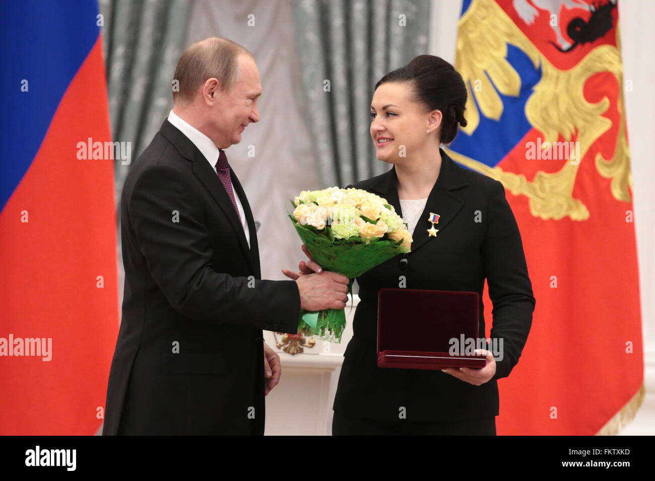Test pilot Yelena Serova of Yu. A. Gagarin Research   Test Cosmonaut  Training Centre (R) receives flowers from Russia s president Vladimir Putin  during a ... 85830a1578b