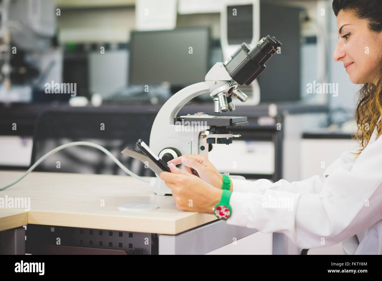 Female scientist using digital tablet and optical microscope - Stock Image