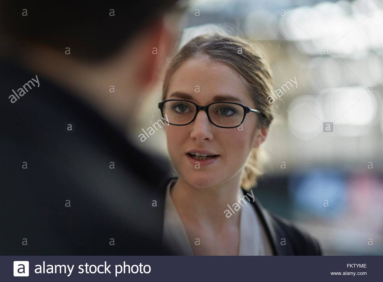 Young businesswoman wearing eye glasses talking to colleague - Stock Image