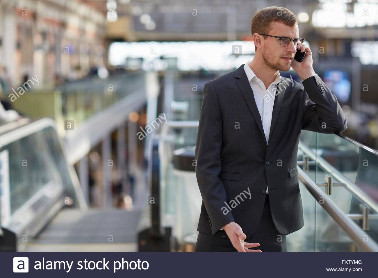 Mid adult businessman leaning against glass panel using smartphone to make telephone call - Stock Image