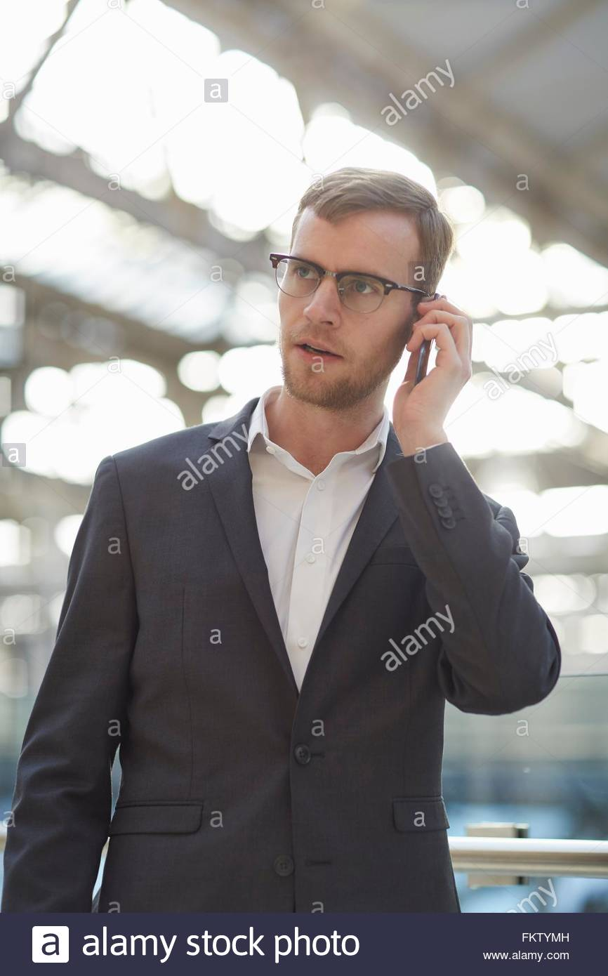 Mid adult businessman using smartphone to make telephone call, looking away - Stock Image