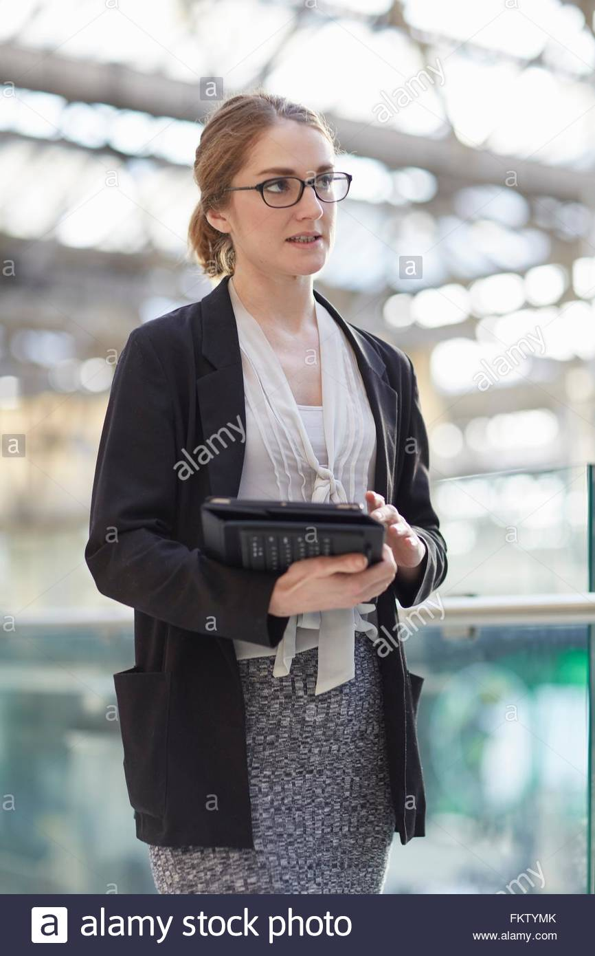 Businesswoman wearing eye glasses holding digital tablet looking away - Stock Image