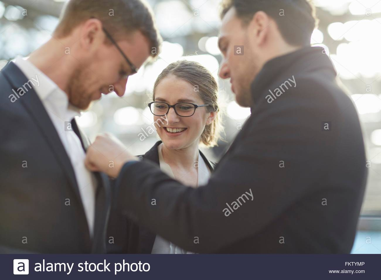 Side view of mid adult man adjusting colleagues pocket handkerchief - Stock Image