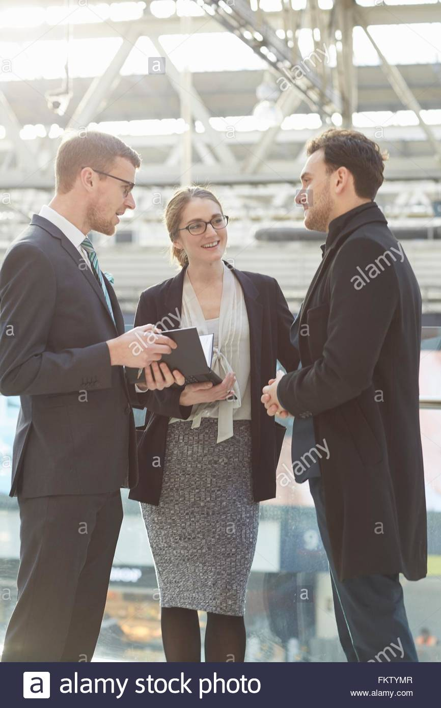 Side view of colleagues standing talking, consulting diary - Stock Image