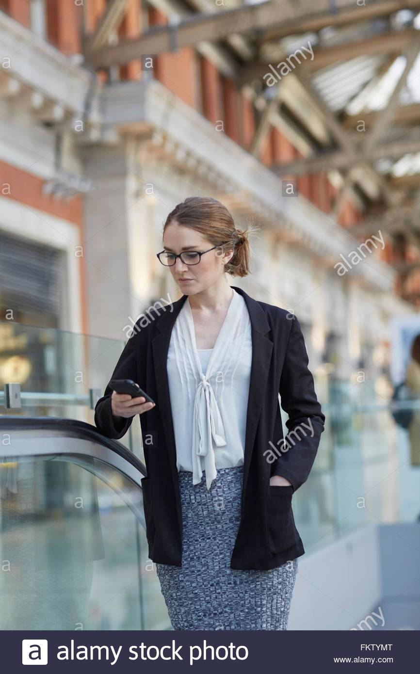Businesswoman on escalator looking down smartphone - Stock Image