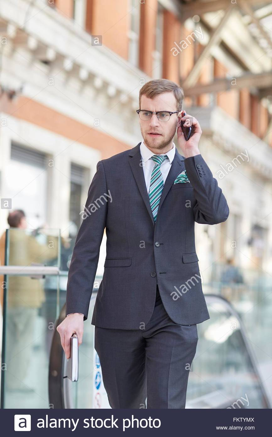 Front view of businessman using smartphone to make telephone call - Stock Image
