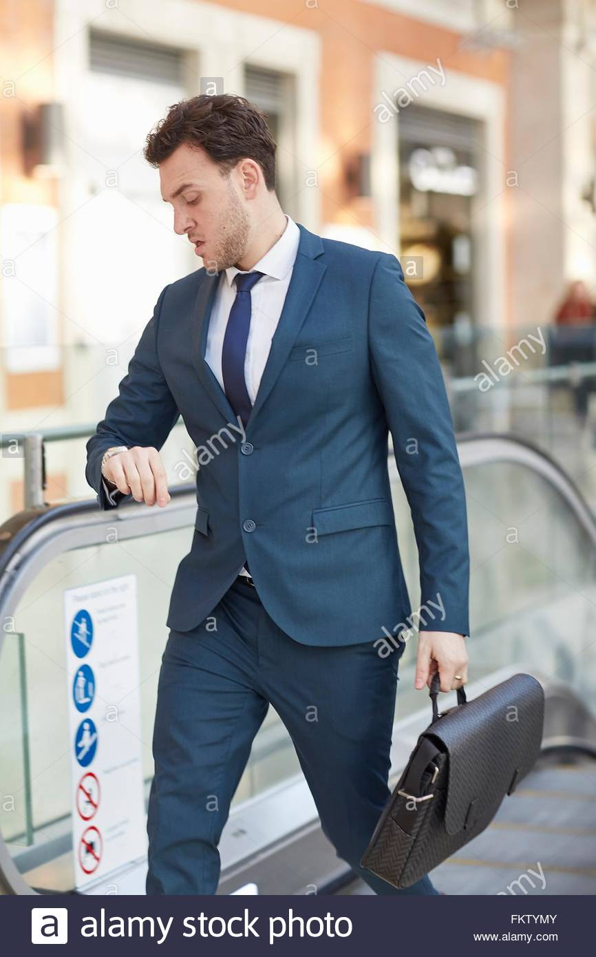 Businessman on escalator carrying briefcase looking down checking wrist watch - Stock Image