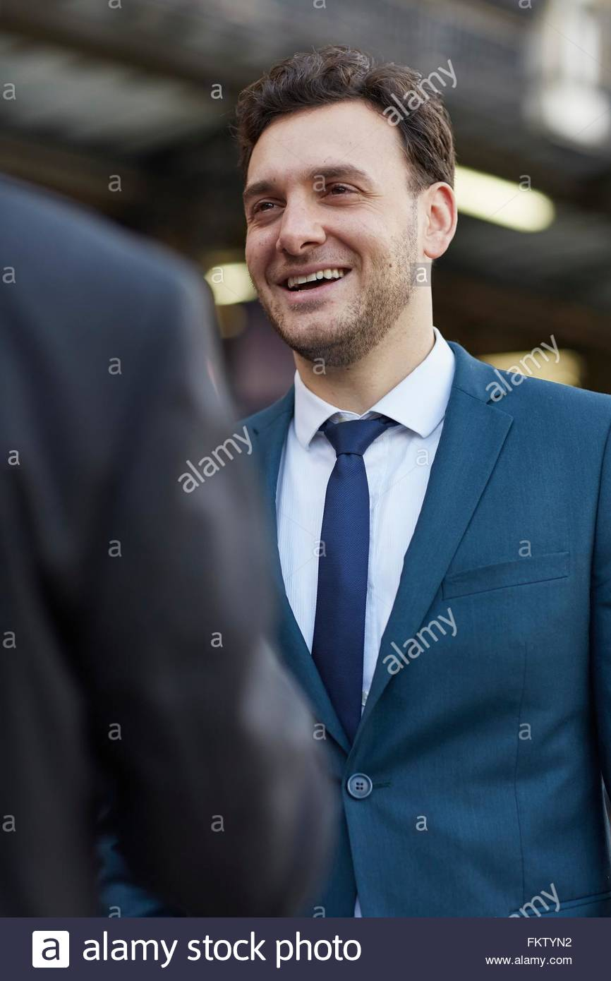 Businessman wearing suit talking to colleague smiling - Stock Image