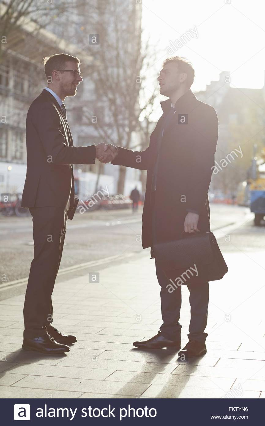 Full length side view of colleagues standing in street face to face talking, smiling, shaking hands - Stock Image