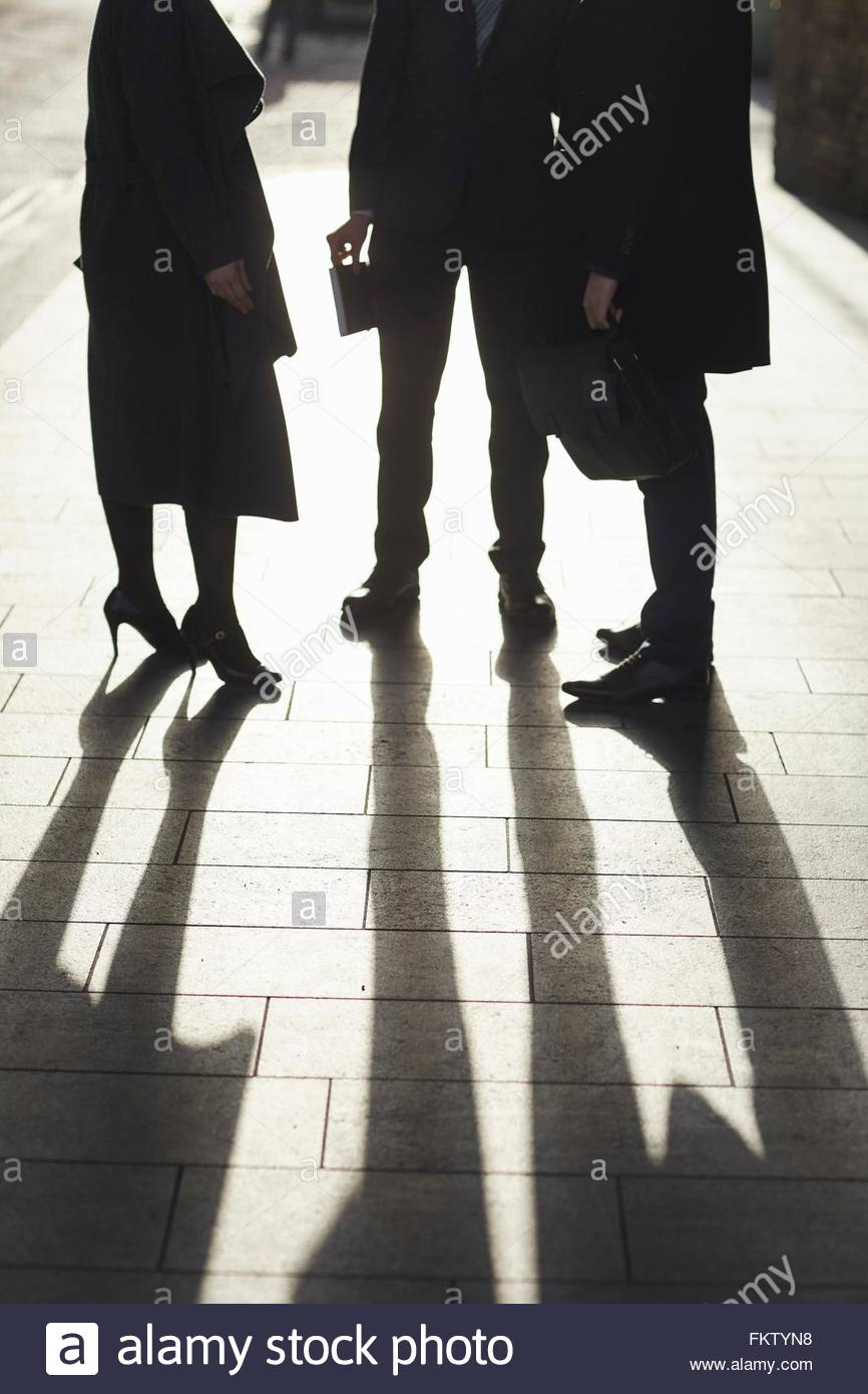 Neck down of business colleagues standing on pavement, face to face - Stock Image