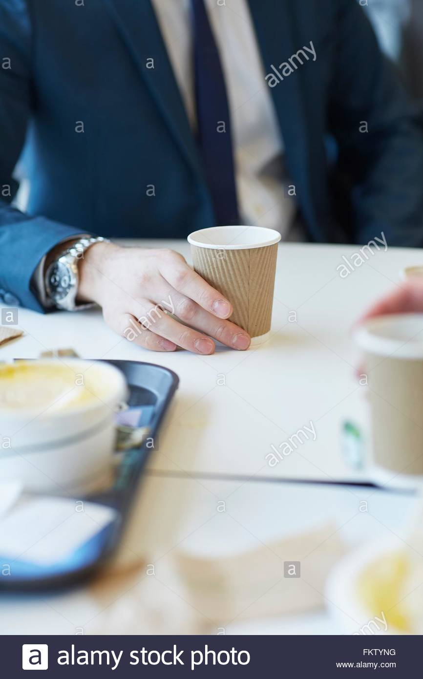 Cropped view of businessman sitting at table holding disposable cup - Stock Image