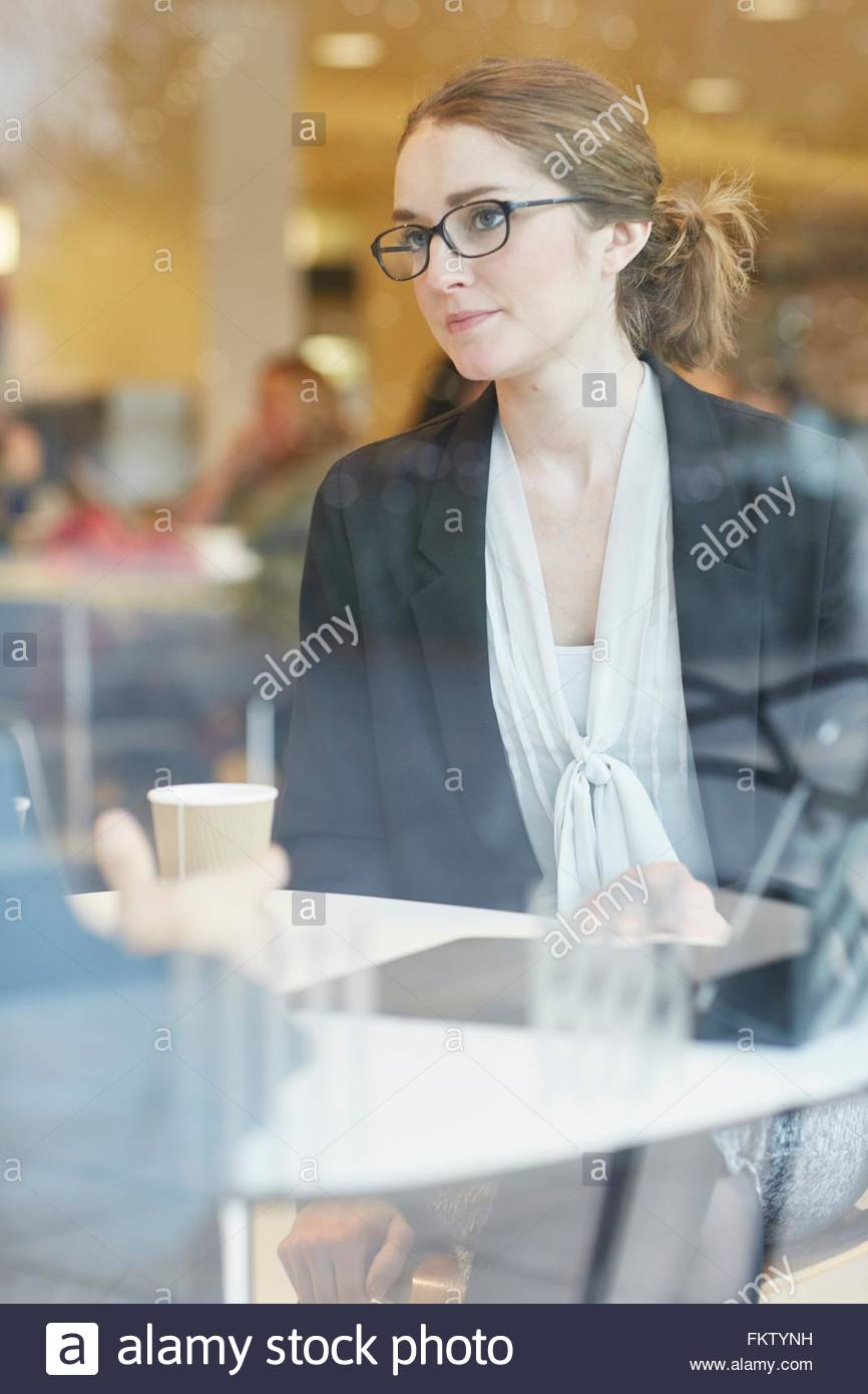 View through window of businesswoman wearing eye glasses sitting at table looking at colleague - Stock Image