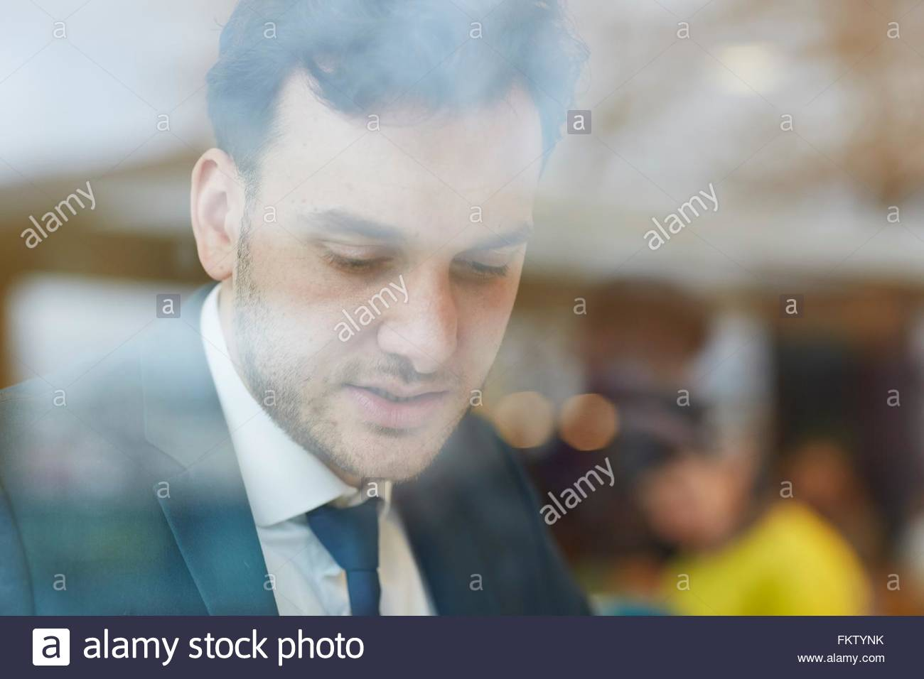 View through window of businessman wearing shirt and tie looking down - Stock Image