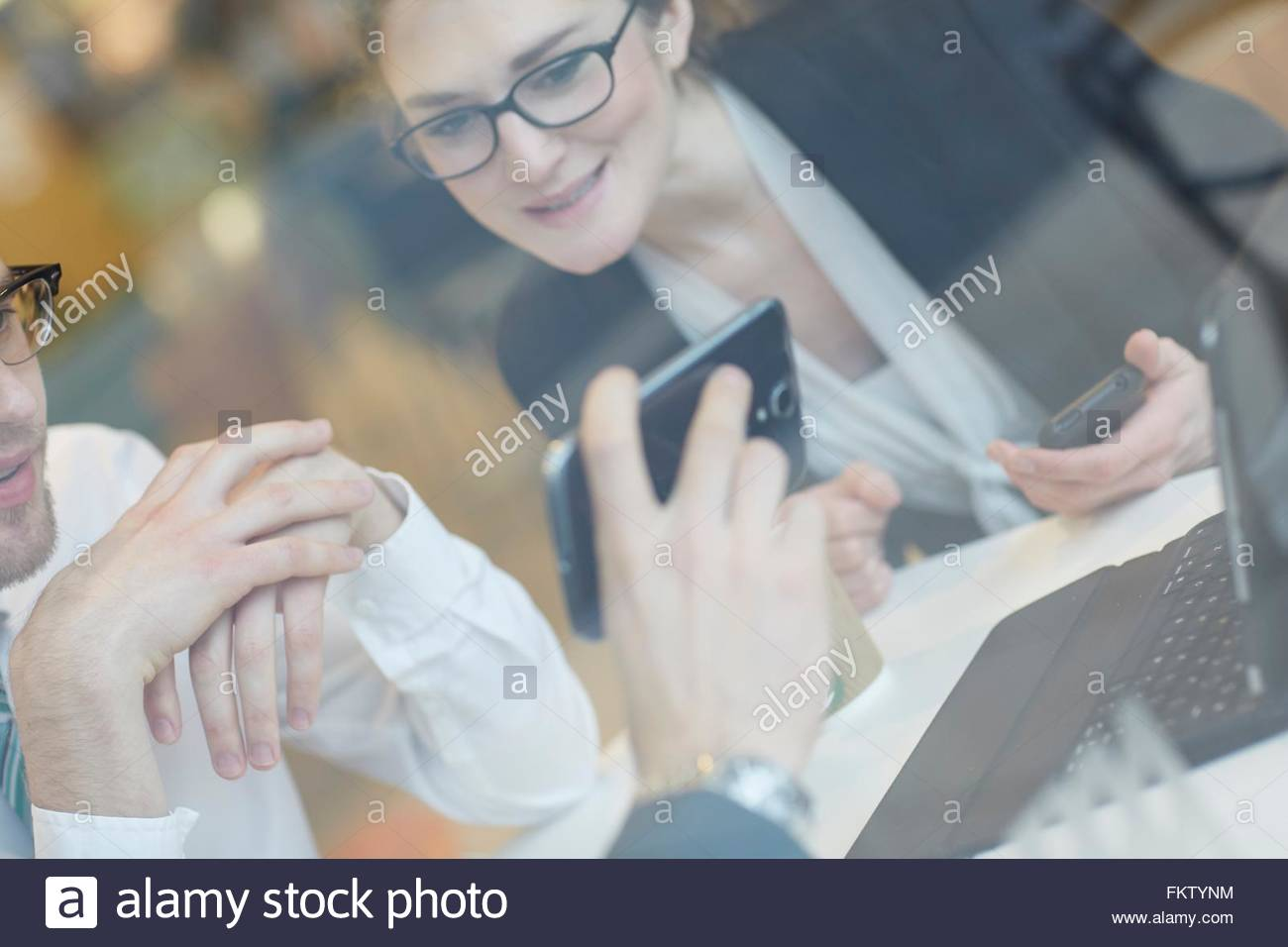 Angled view through window of colleagues wearing eye glasses looking at smartphone smiling - Stock Image