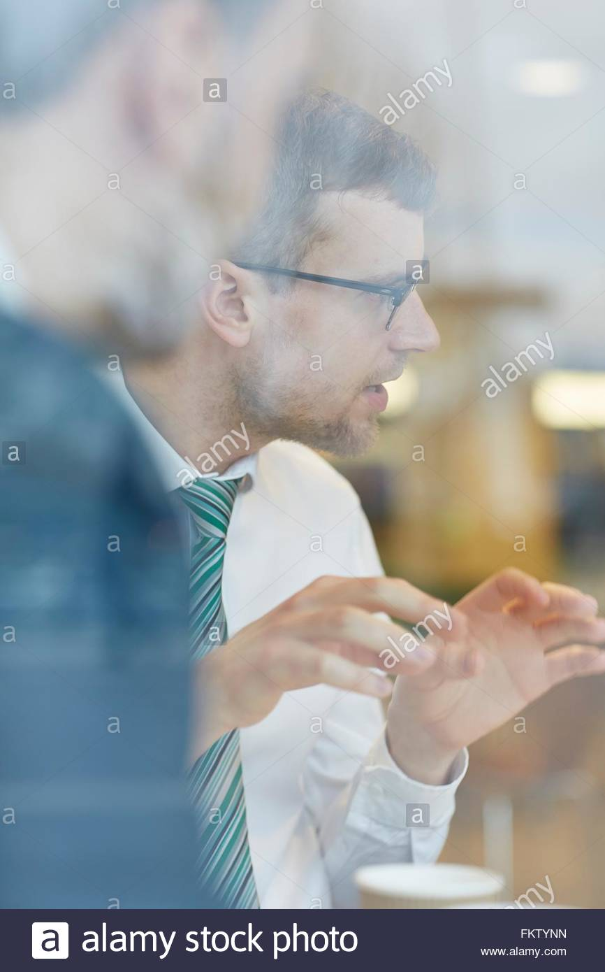 View through window of businessman wearing eye glasses with shirt and tie, talking, hand gestures - Stock Image
