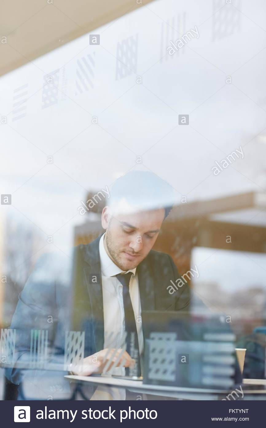 View through window of businessman sitting at table texting, looking down - Stock Image