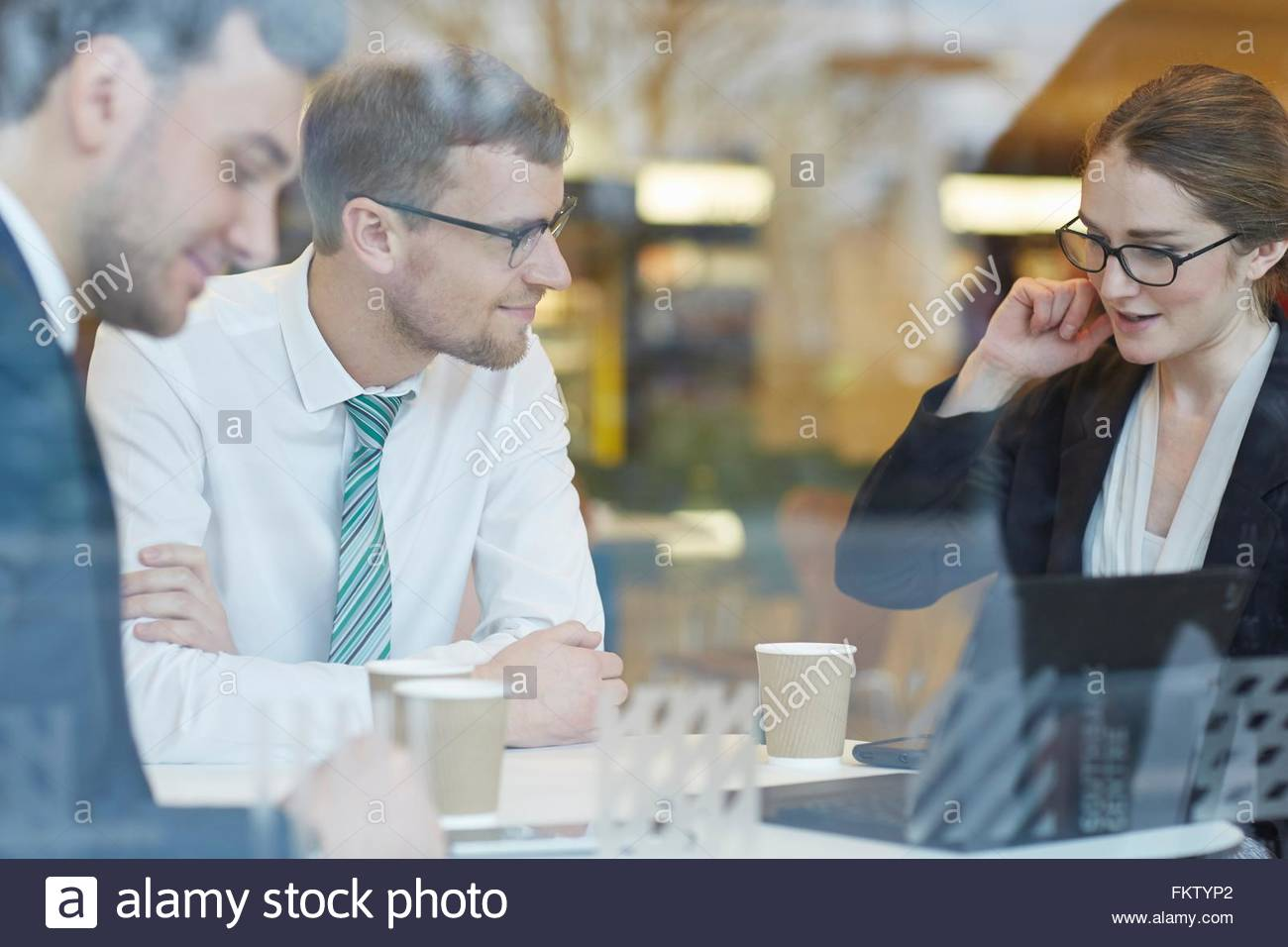 View through window of business colleagues wearing eye glasses sitting at table drinking coffee, talking - Stock Image