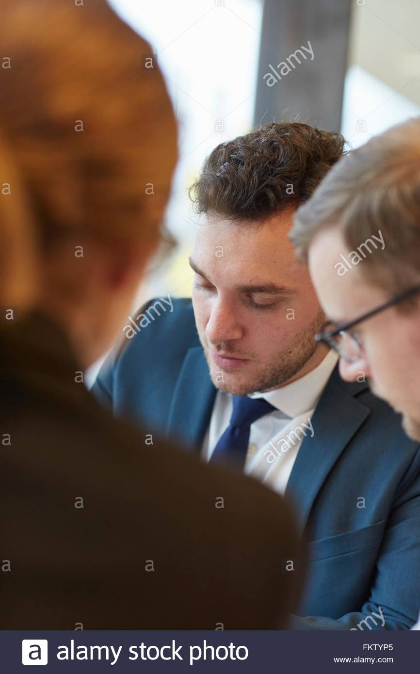 Young man wearing shirt and tie in business meeting looking down - Stock Image