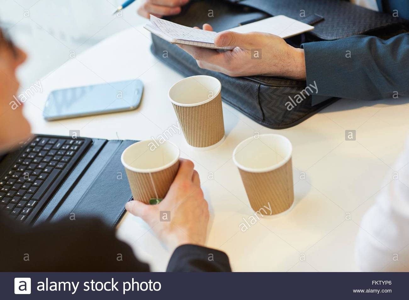 High angle view of colleagues in meeting holding notebook and disposable cups - Stock Image