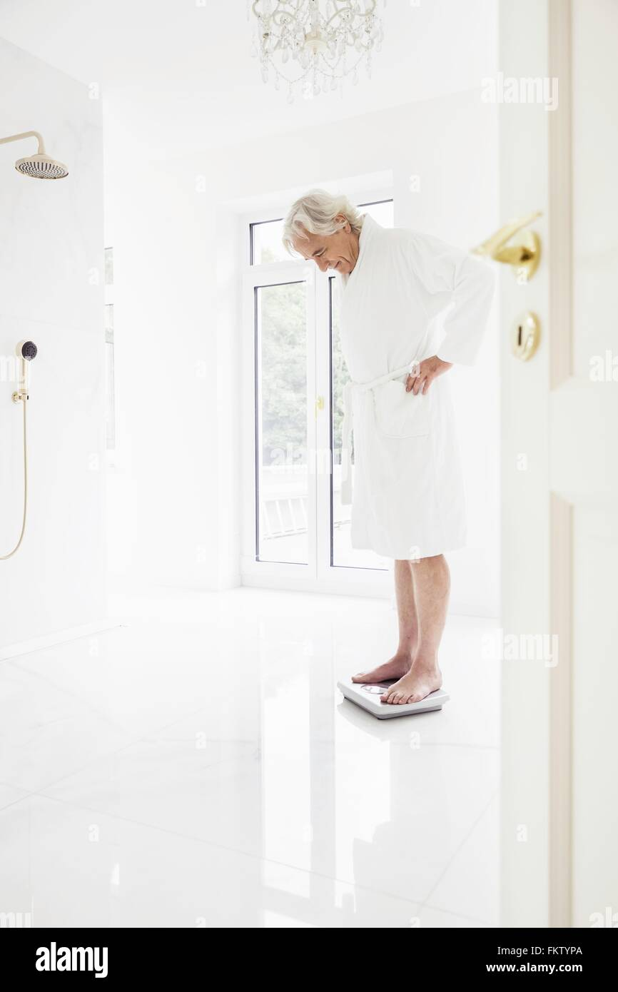 Happy grey haired senior man wearing bathrobe weighing himself on bathroom scales - Stock Image