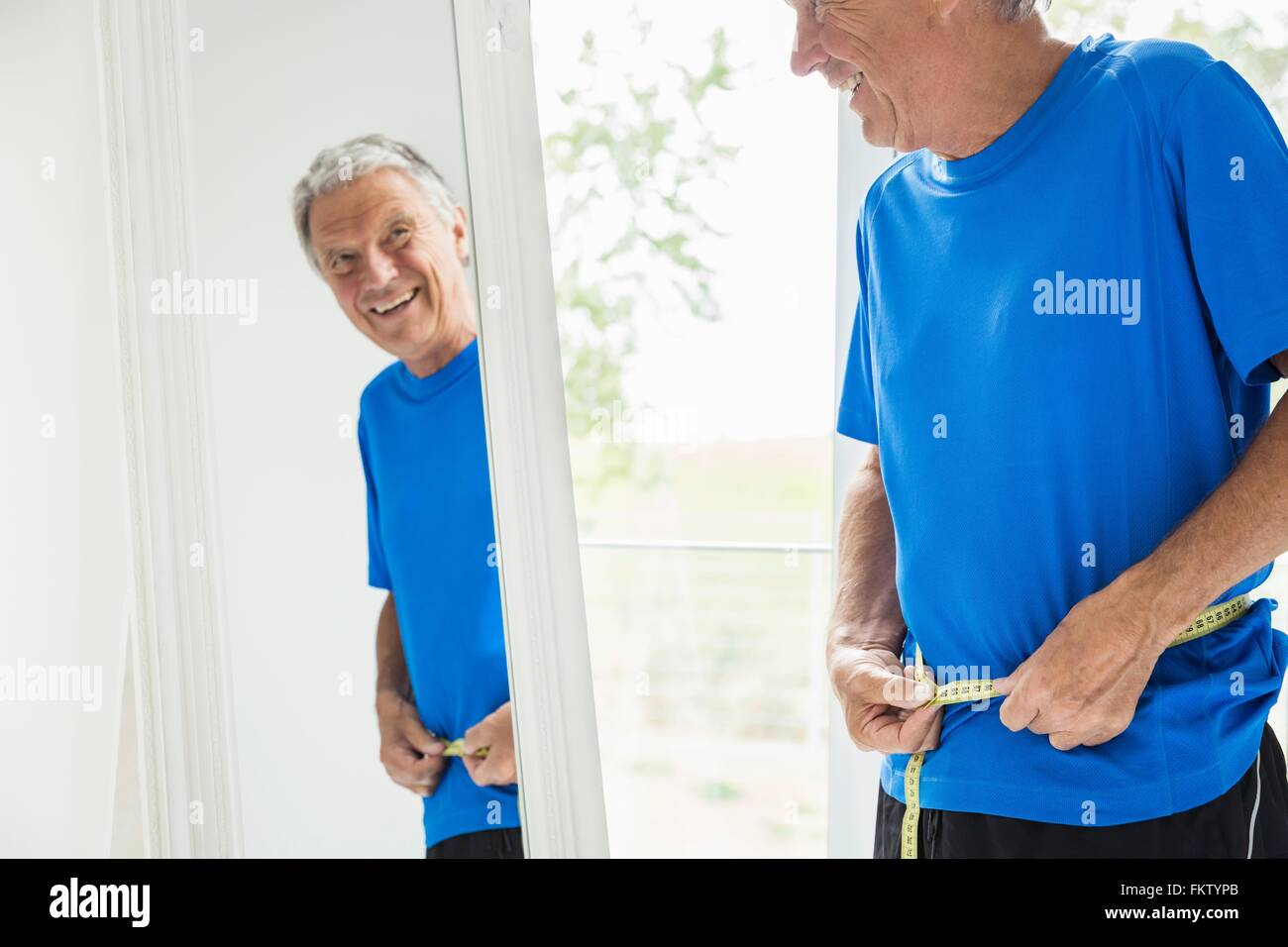 Happy senior man measuring his waist whilst looking in mirror - Stock Image