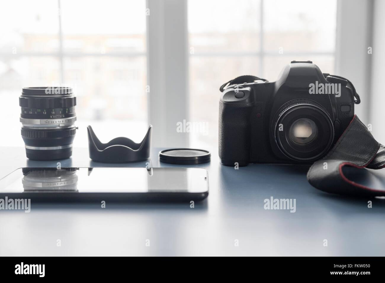 Digital tablet and digital SLR camera on studio desk - Stock Image