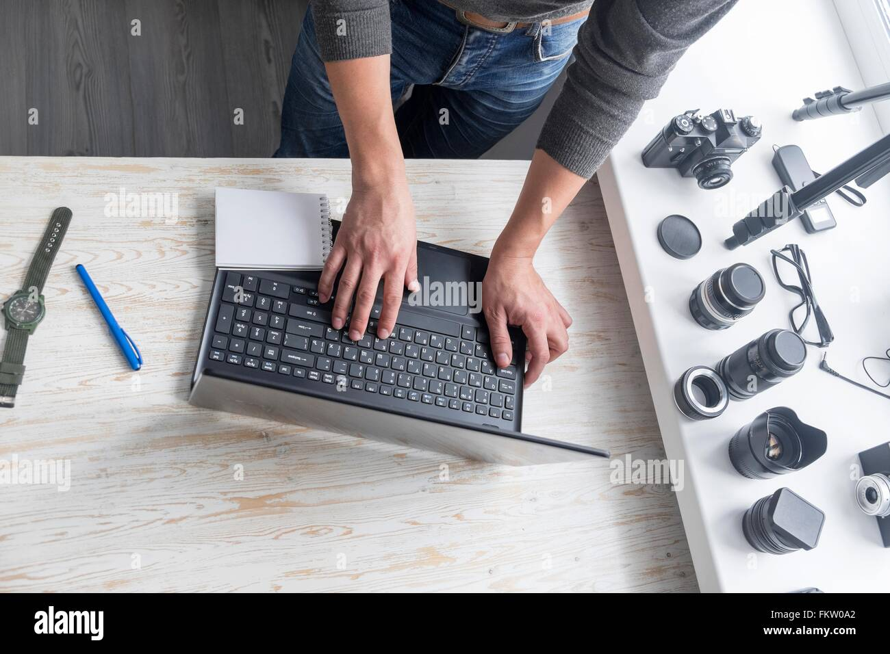 Overhead view of male photographer typing on studio desk laptop Stock Photo