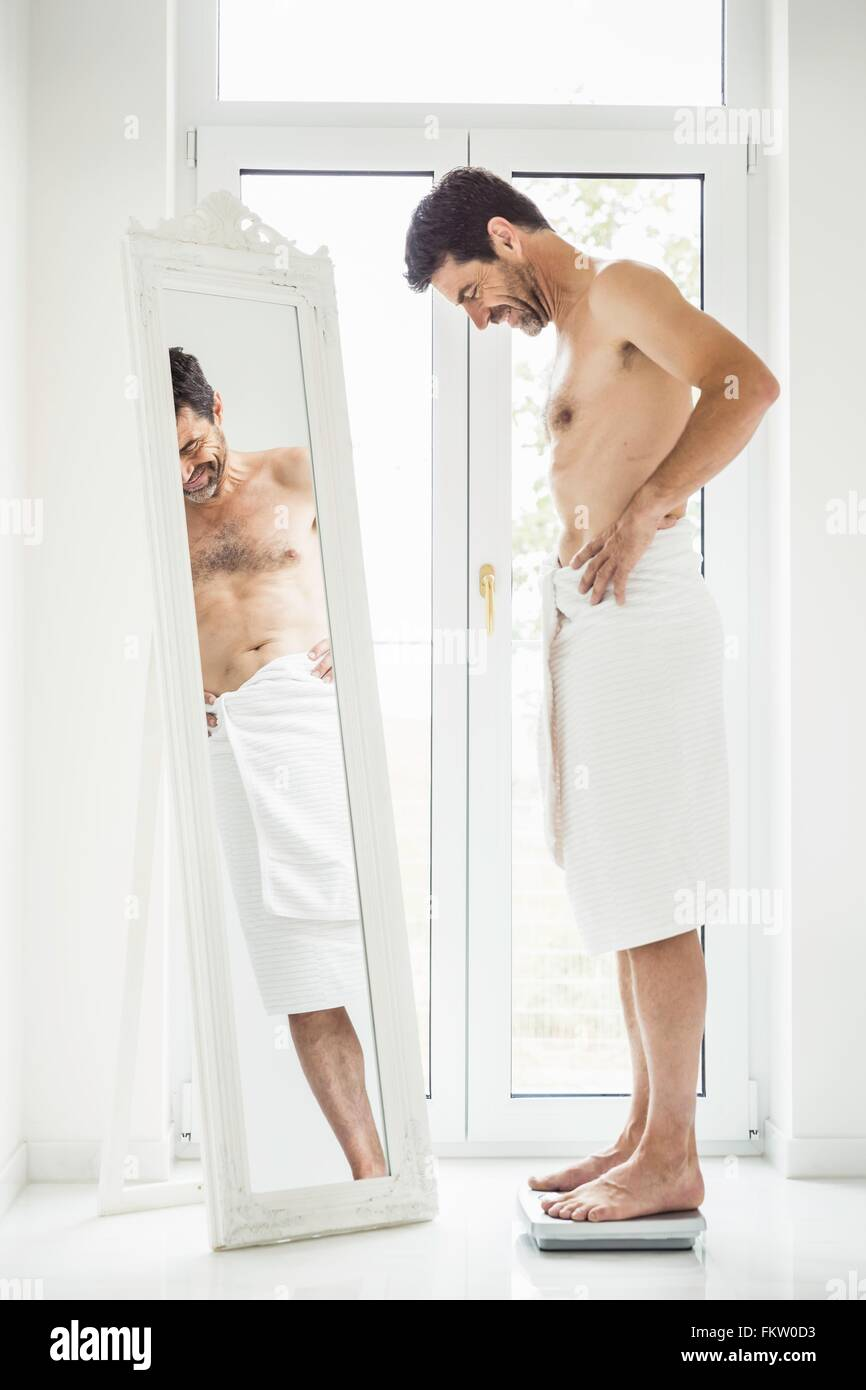 Happy mature man wrapped in towel weighing himself on bathroom scales - Stock Image