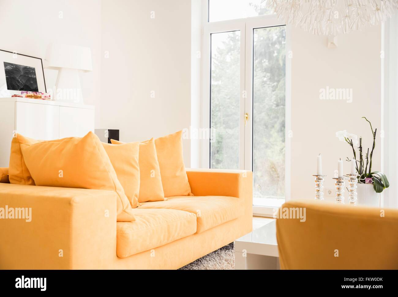 Stylish living room with yellow sofas and patio door - Stock Image