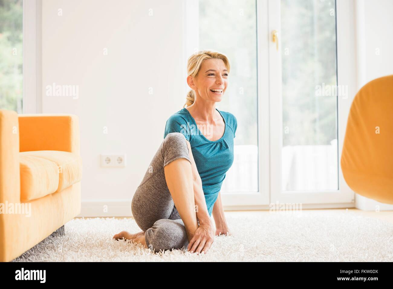 Mature woman doing stretch exercise in living room floor - Stock Image