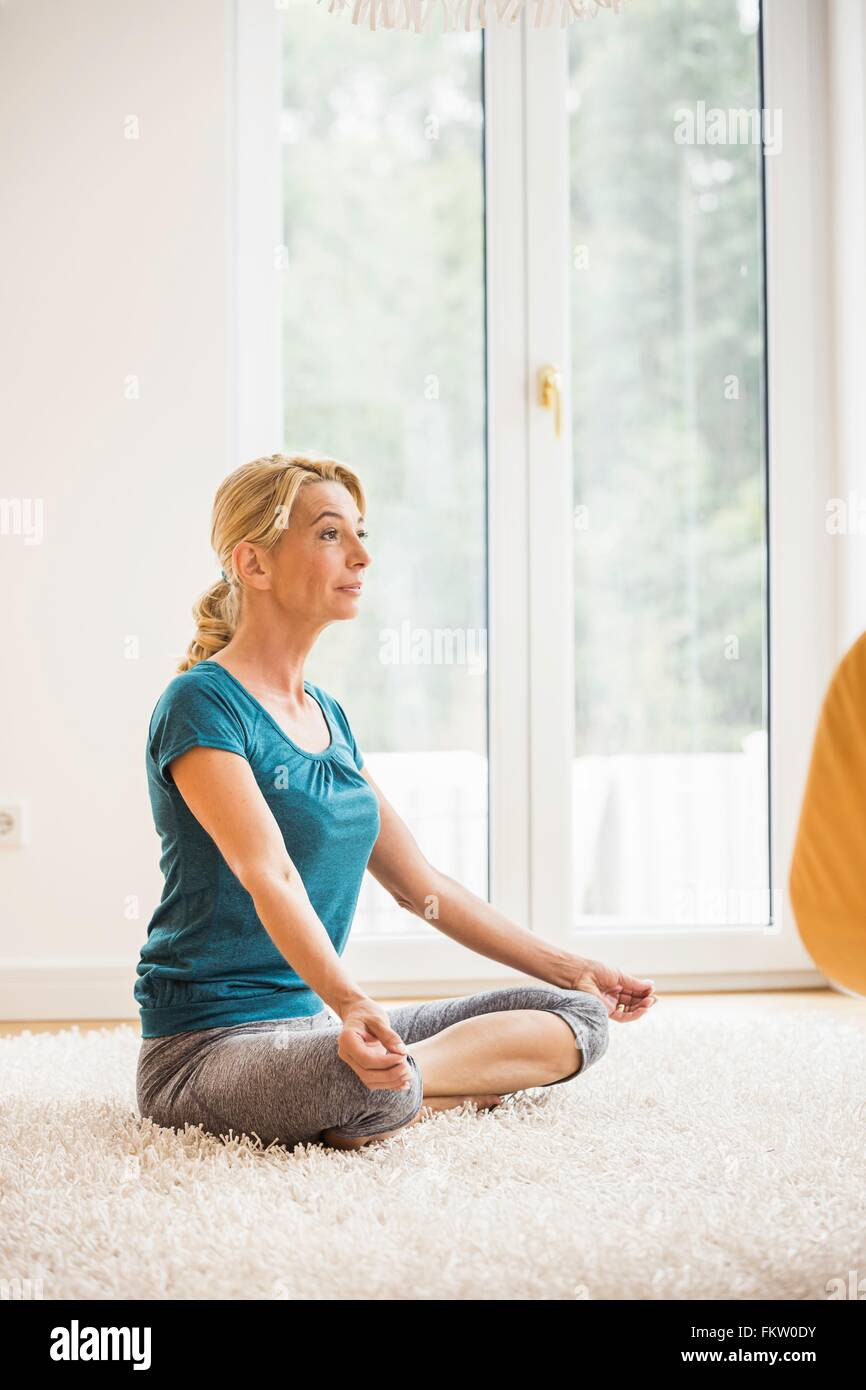 Mature woman practicing yoga lotus position on living room floor - Stock Image