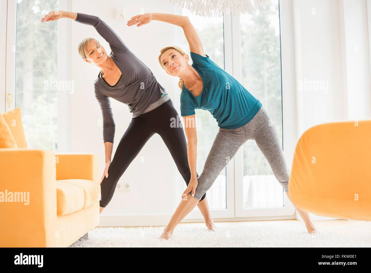 Two mature women bending over sideways whilst exercising in living room - Stock Image