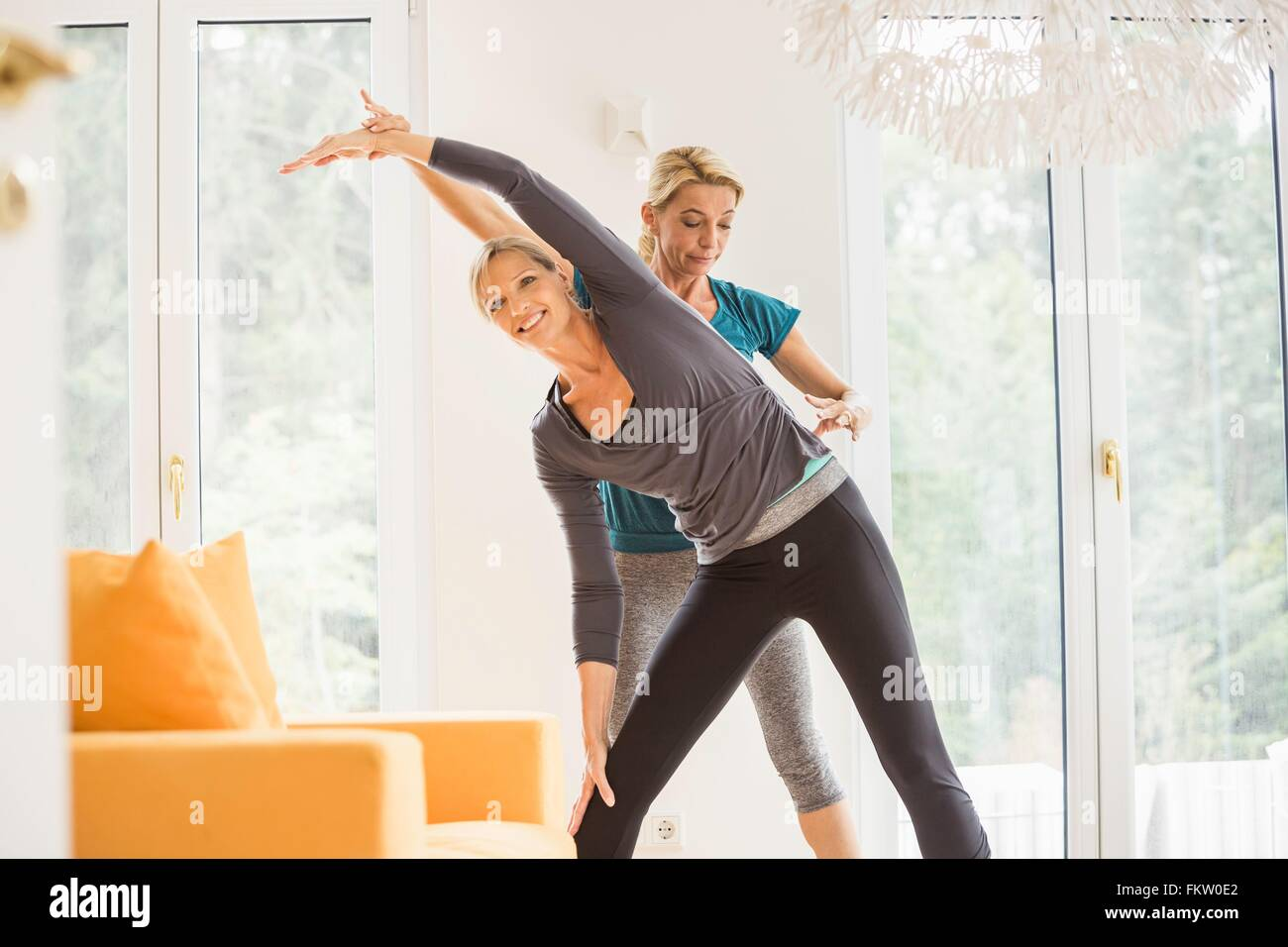 Mature woman and personal trainer exercising in living room - Stock Image