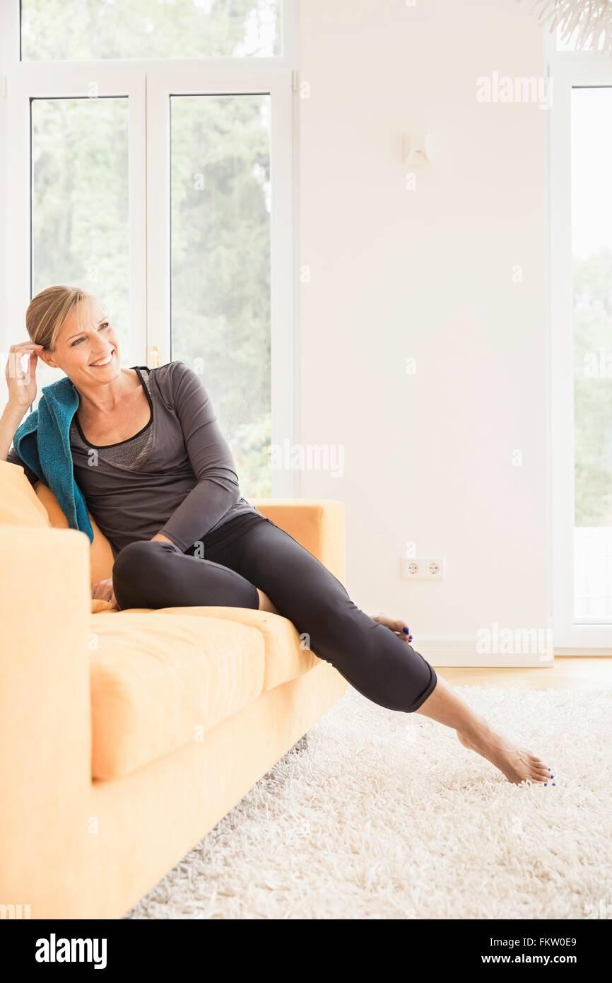 Mature woman taking an exercise break on living room sofa - Stock Image