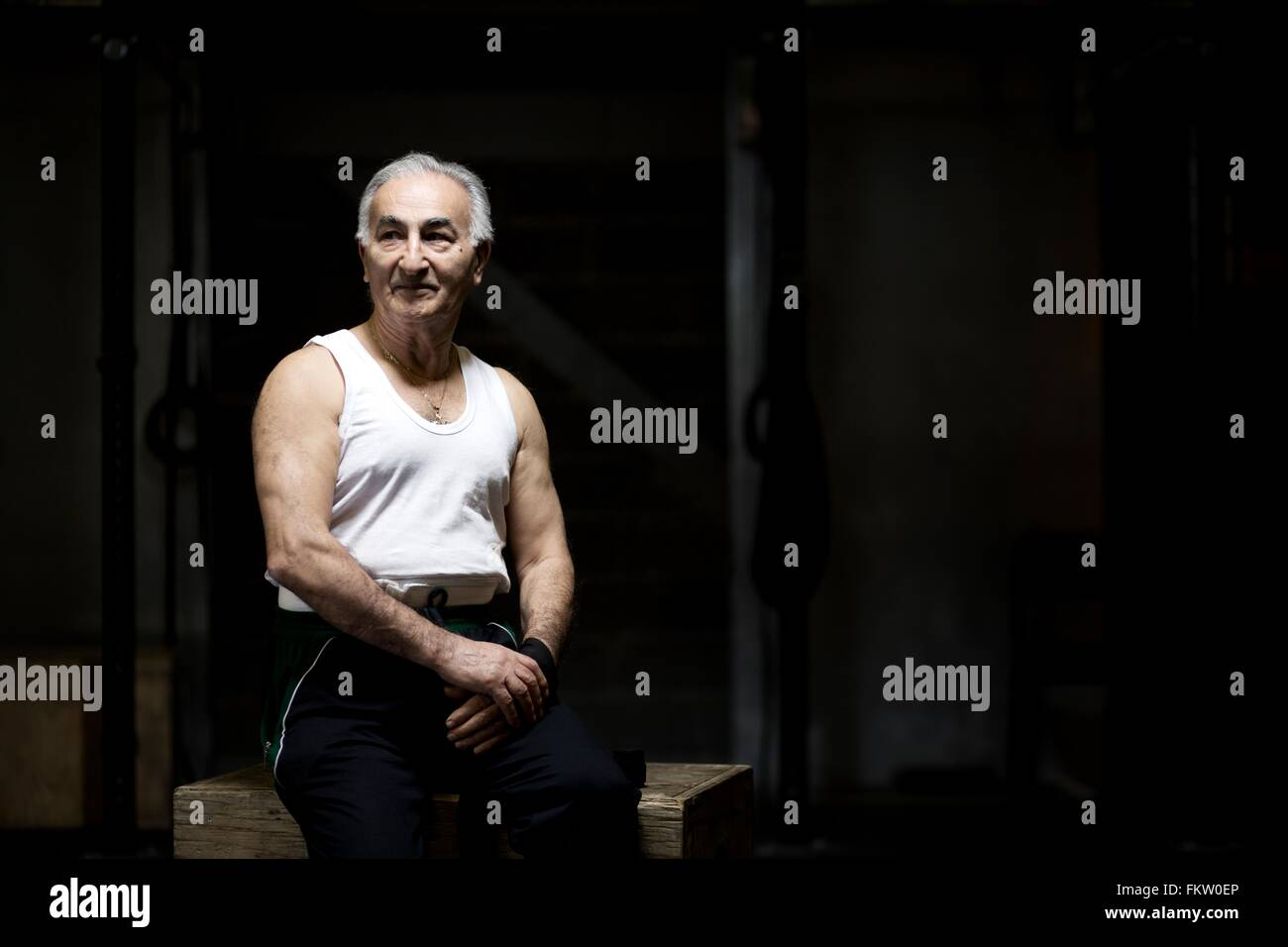 Portrait of grey haired senior man sitting in dark gym - Stock Image