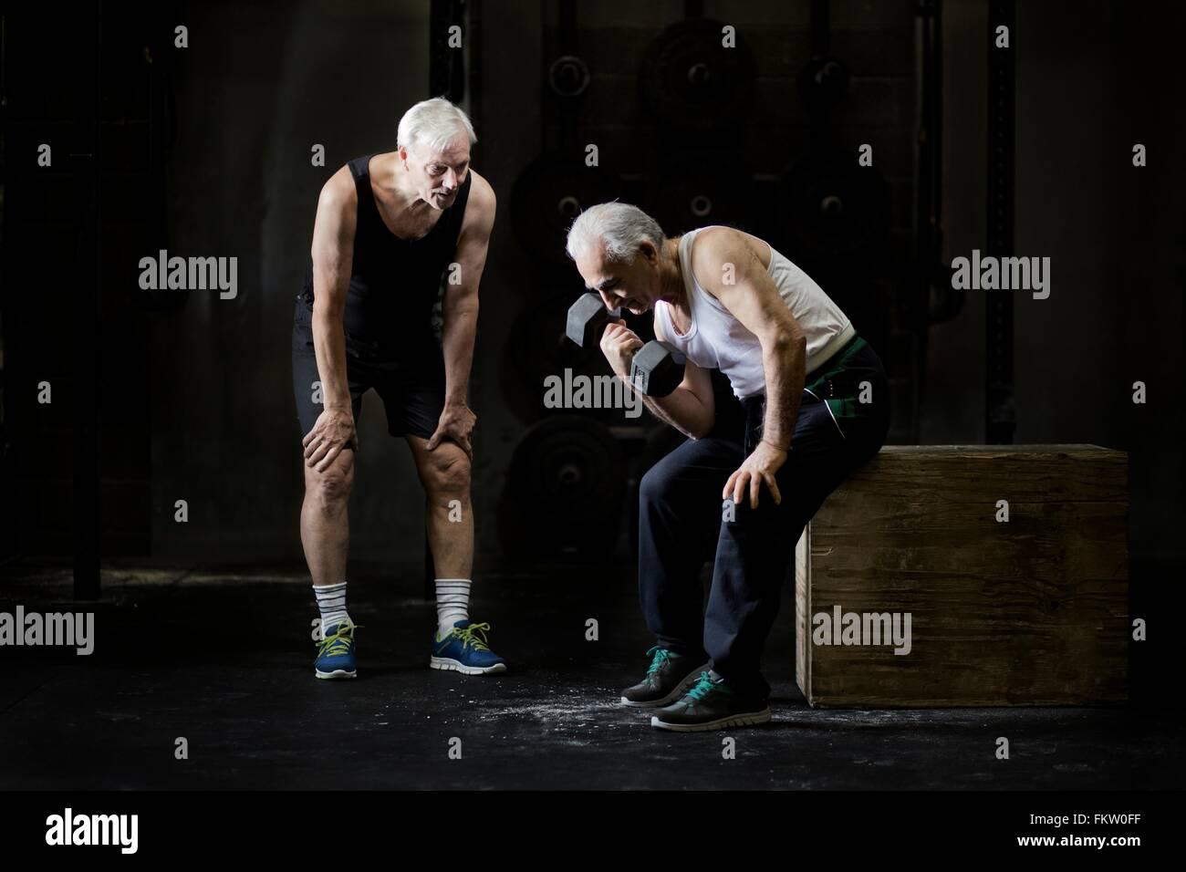 Senior men training with dumbbell in dark gym - Stock Image