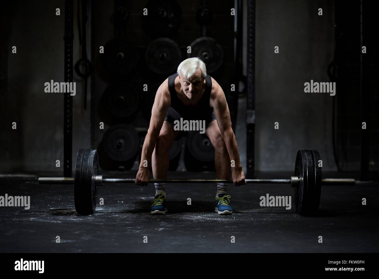 Senior man preparing to weightlift barbell in dark gym - Stock Image