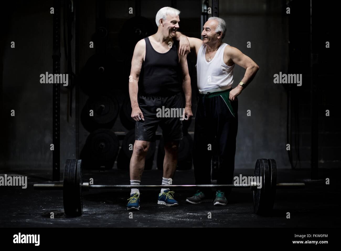Senior men chatting in dark gym - Stock Image