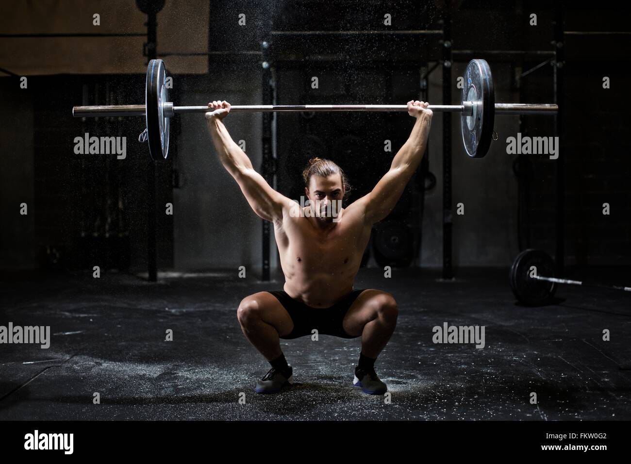 Bare chested young man weightlifting barbell in dark gym Stock Photo