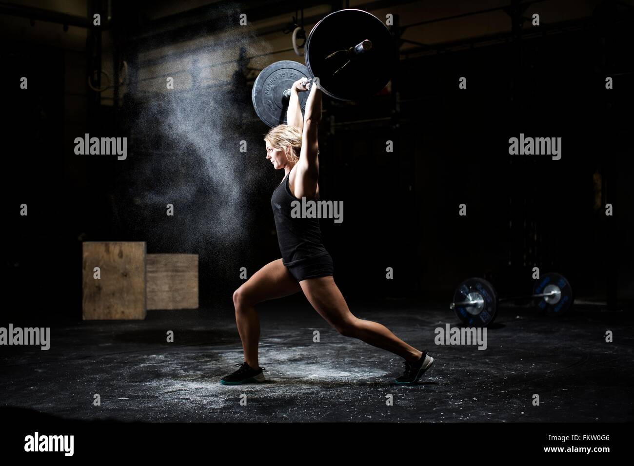 Side view of young woman weightlifting barbell in dark gym Stock Photo