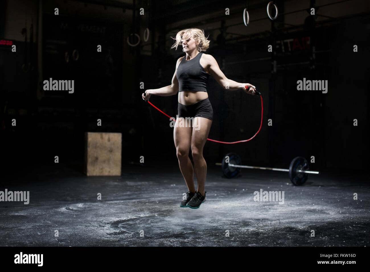 Young woman skipping in dark gym - Stock Image