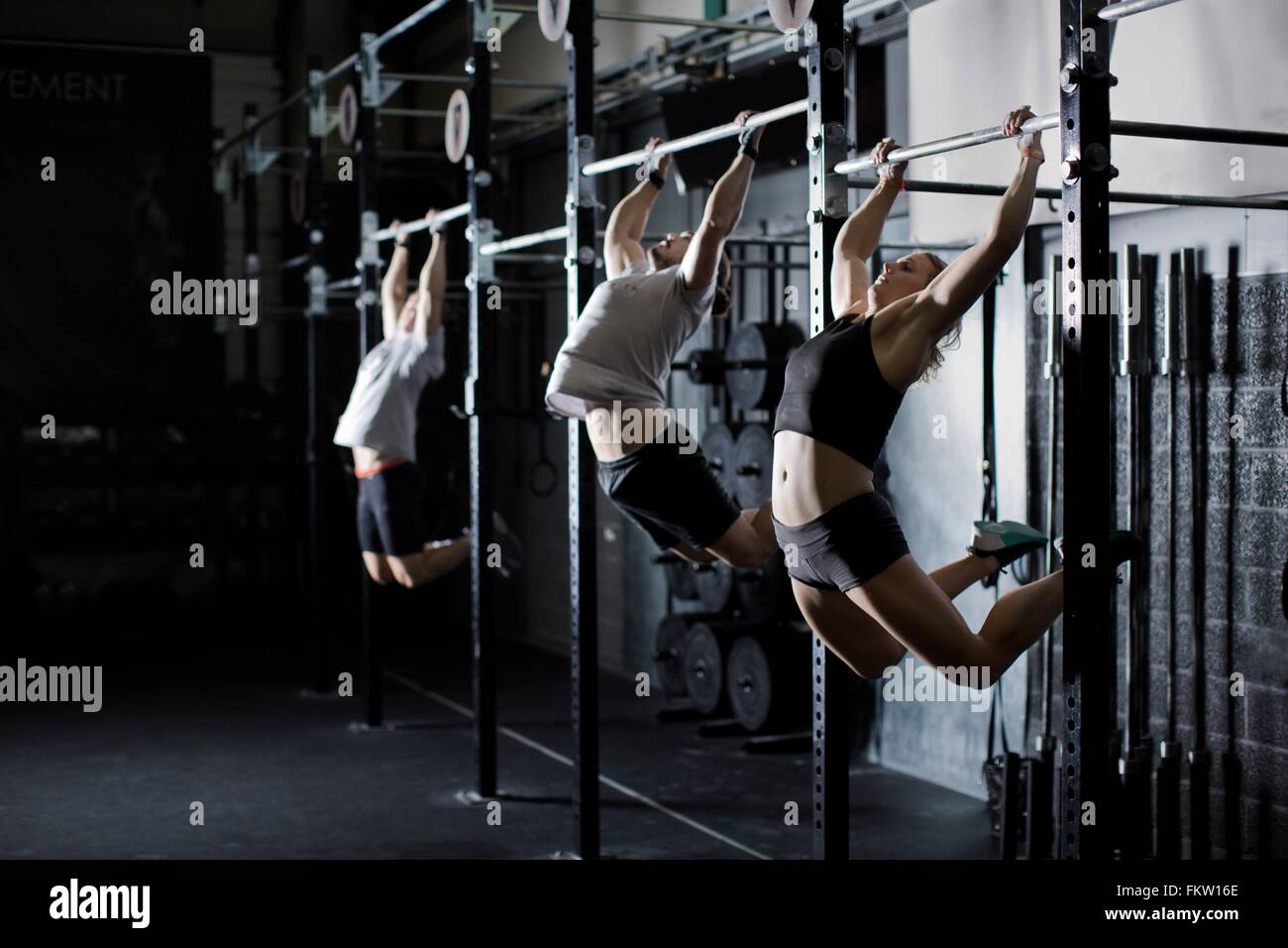 Male and female young adults training on wall bar in gym - Stock Image