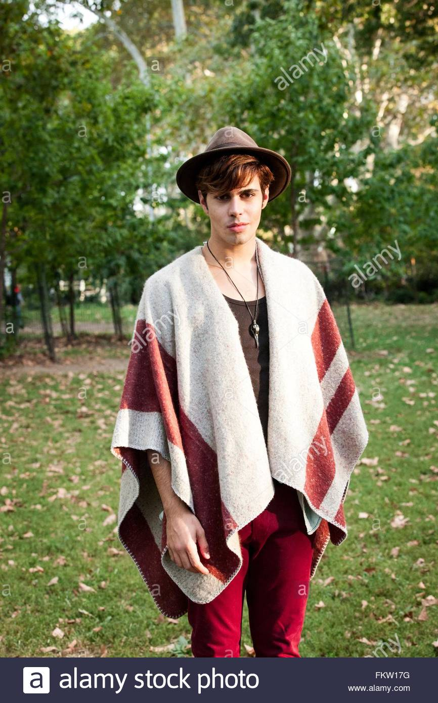 Portrait of young male hipster wearing a poncho and trilby in park - Stock Image