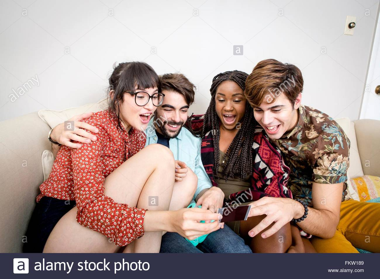 Two young hipster couples sitting on apartment sofa laughing at instant photograph - Stock Image